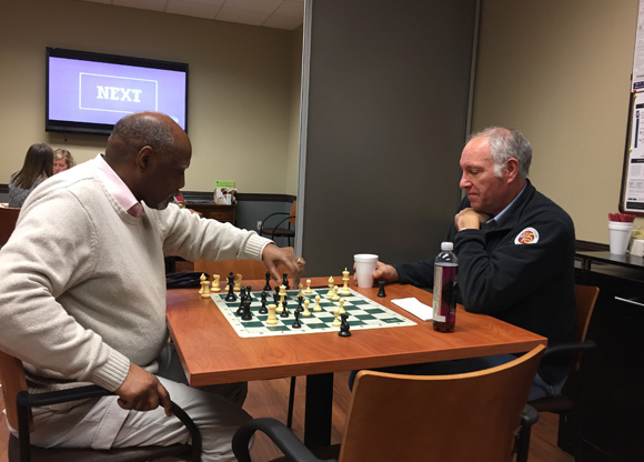 Two men play chess in an ICT break room during lunch