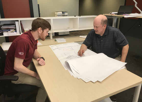 Two mechanical consulting engineers work together to analyze a drawing
