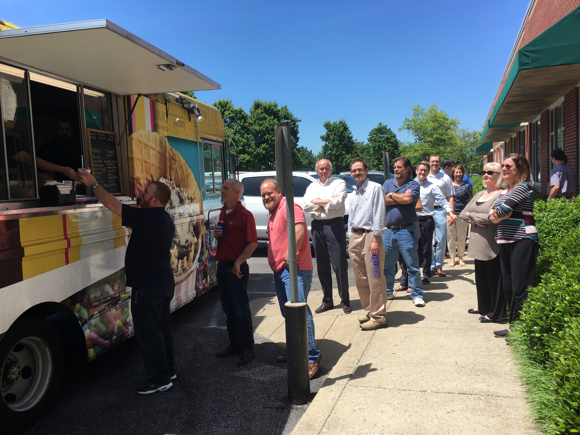 ICT employees line up to enjoy a visit from a food truck that stopped by the office on a pretty day